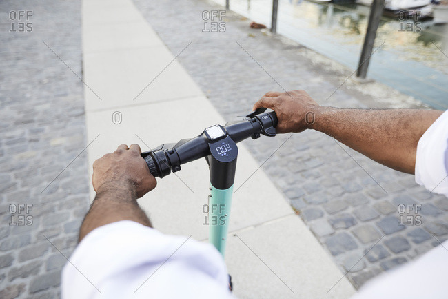 Hands of mature man on handlebar of E-Scooter