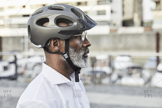 Profile of mature businessman with grey beard wearing cycling helmet and glasses
