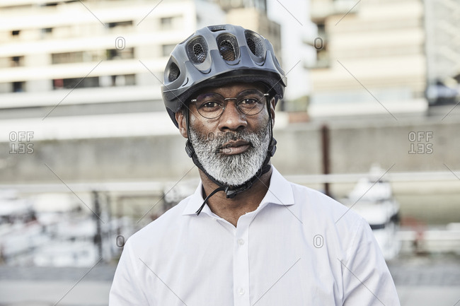 Portrait of mature businessman with grey beard wearing cycling helmet and glasses