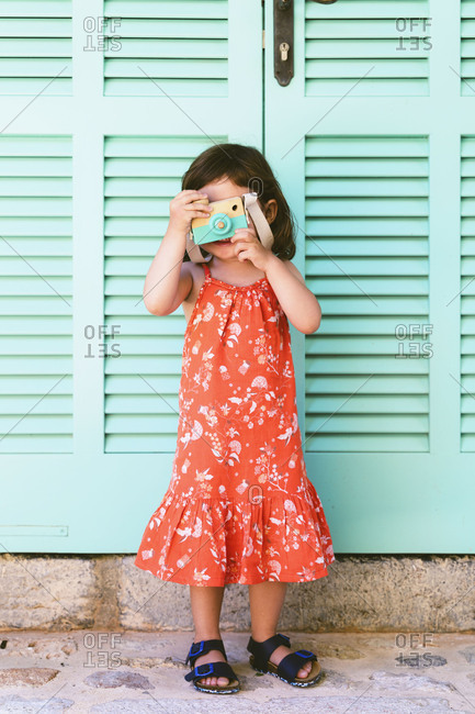 Little girl playing with wooden toy camera wearing red dress with floral design
