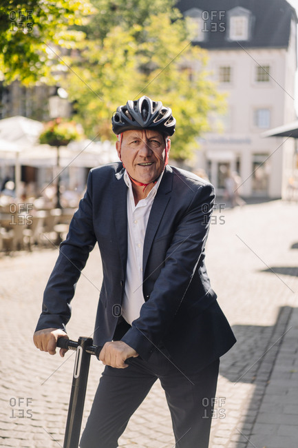 Portrait of smiling senior man with e-scooter in the city