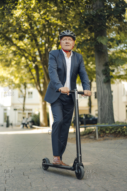 Senior man riding e-scooter in the city