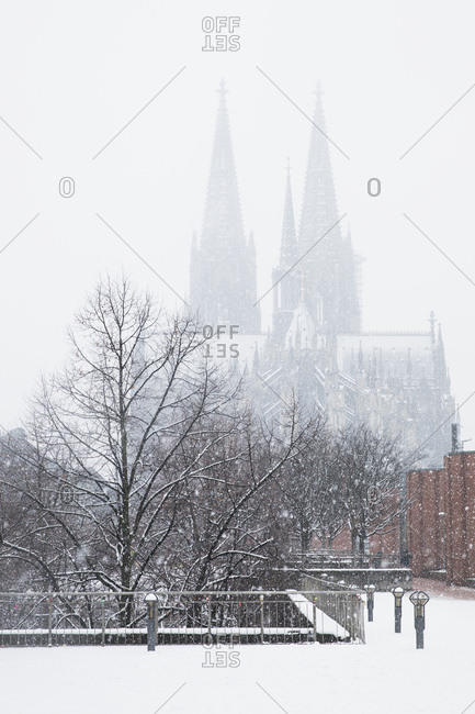 Bare trees against Cologne Cathedral during snowfall in city against sky