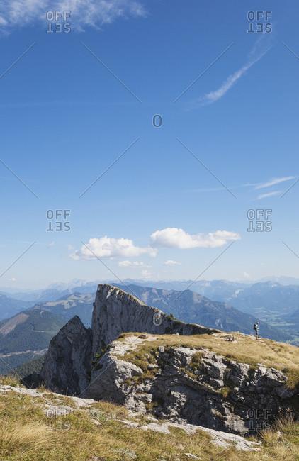 Distant view of hiker standing on Spinnerin peak against blue sky