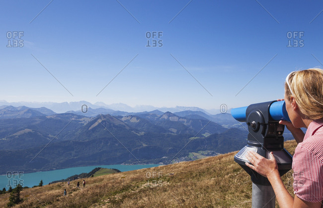 Woman looking at mountains through coin-operated binoculars from Schafberg against blue sky