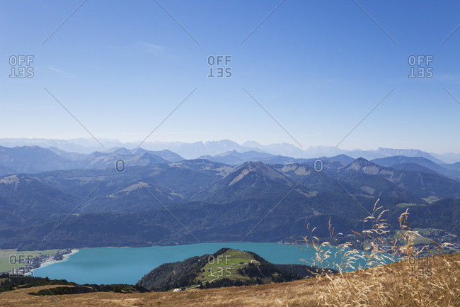 Scenic view of Lake Wolfgangsee and mountains against blue sky