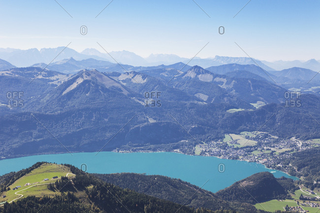 Scenic view of Wolfgangsee by Saint Gilgen and European Alps against blue sky