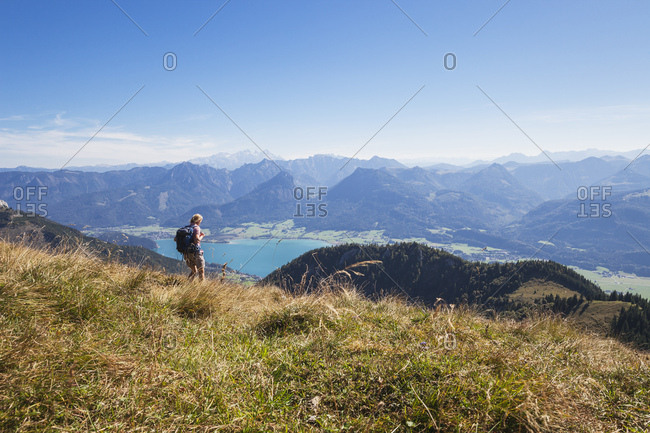 Mature woman hiking on grass at Schafberg Railway with Lake Wolfgangsee and Dachstein Mountains against blue sky