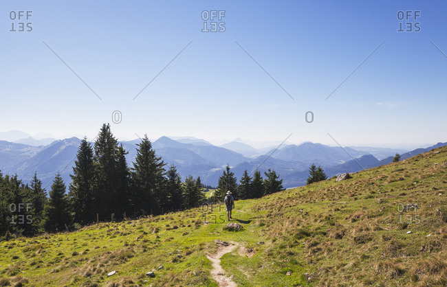 Full length rear view of man hiking on Schafberg peak during sunny day