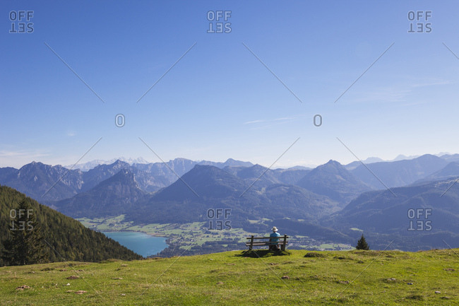 Rear view of senior male hiker sitting on bench while looking at Dachstein Mountains against blue sky