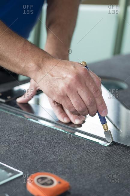 Glazing- glazier during work- cutting glass with glass cutter