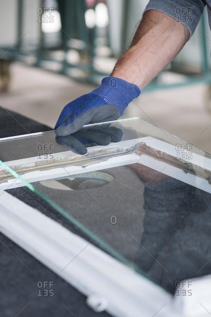 Glazing- glazier during work- inserting glass pane