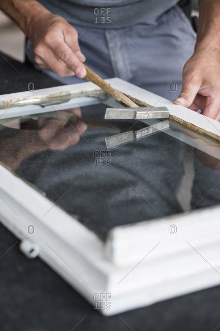 Glazing- glazier during work- hammering