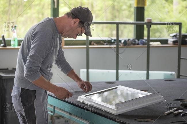 Glazing- glazier during work with tool on window frame
