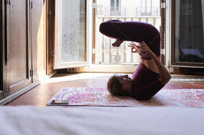 Young brunette woman practicing yoga in student dorm