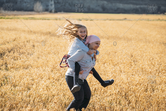 A woman with cancer carrying her daughter on her back- laughing