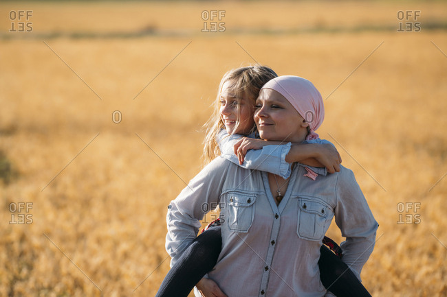 A woman with cancer carrying her daughter on her back- looking sideways