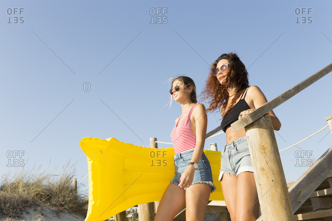 Young women with yellow airbed walking to the beach