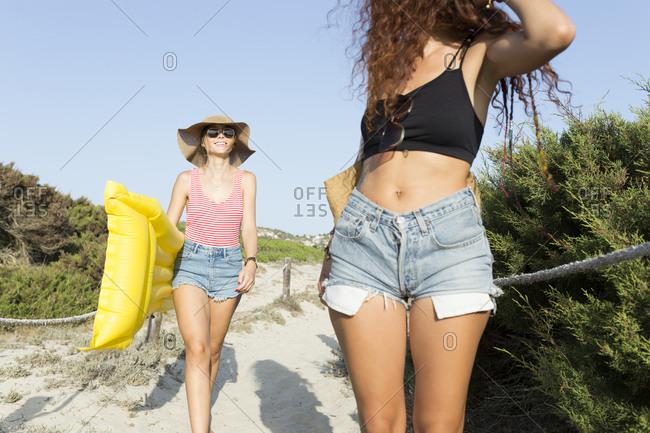 Young women walking to the beach