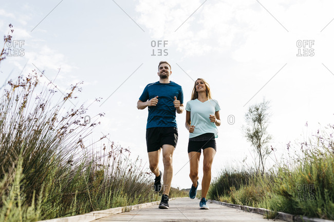 Young couple jogging on wooden walkway