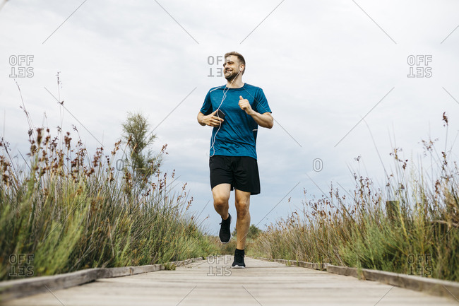 Jogger with earphones running on a wooden walkway