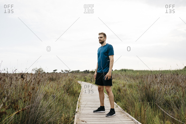 Jogger with earphones and smartphone standing on a wooden walkway