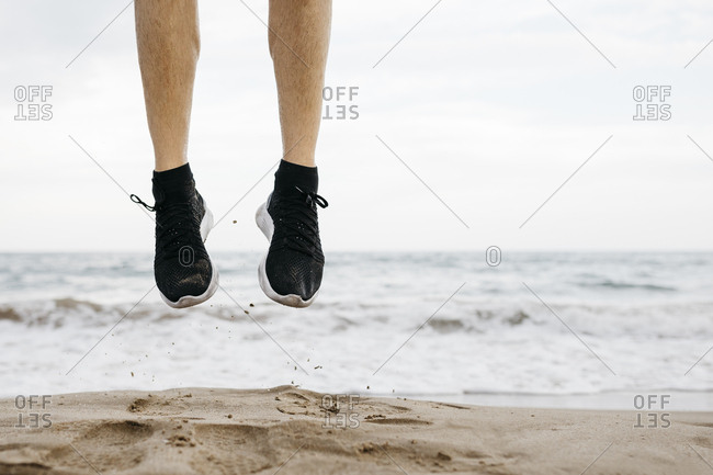 Legs of man jumping on the beach while training