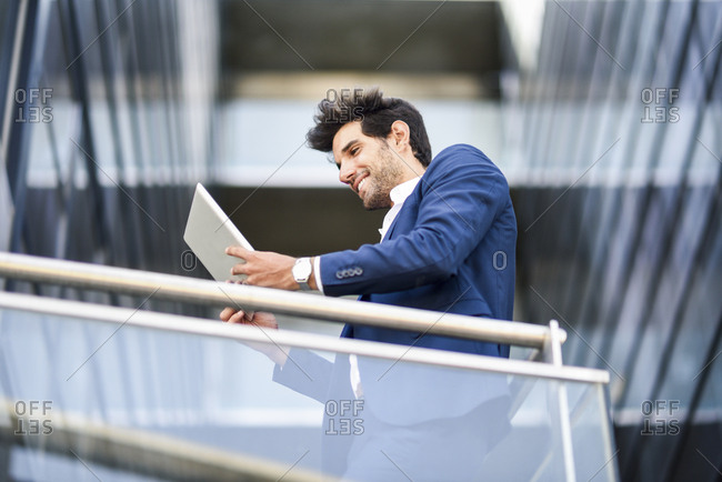 Smiling businessman using tablet on balcony of an office building