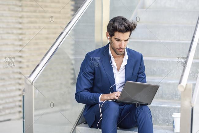 Businessman wearing earphones using laptop outdoors in the city