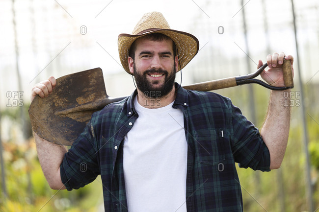 Portrait of smiling young man holding a shovel in a greenhouse
