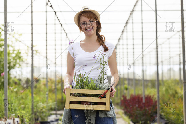 Portrait of beautiful young woman holding wooden box with plants in the greenhouse