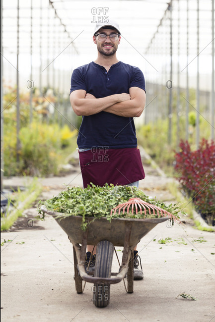 Portrait of young man with wheelbarrow in the greenhouse