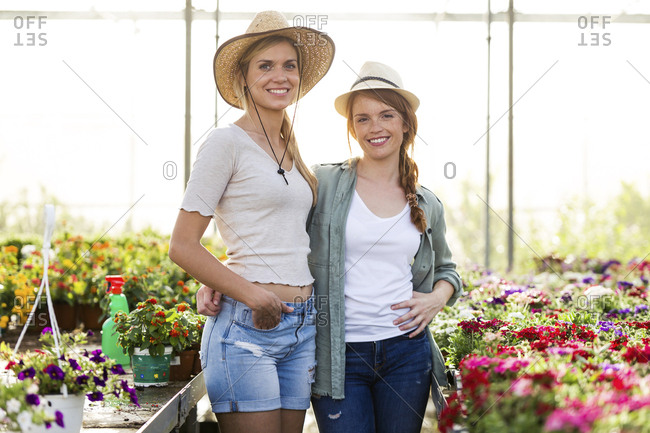 Portrait of two young beautiful women in the greenhouse