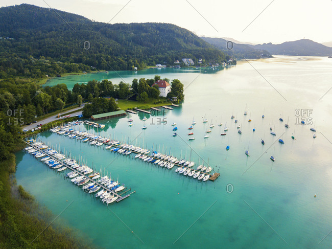 Aerial view of boats moored by jetty in Woerthersee at harbor against sky during sunset
