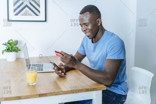 Young man with credit card and smartphone at home