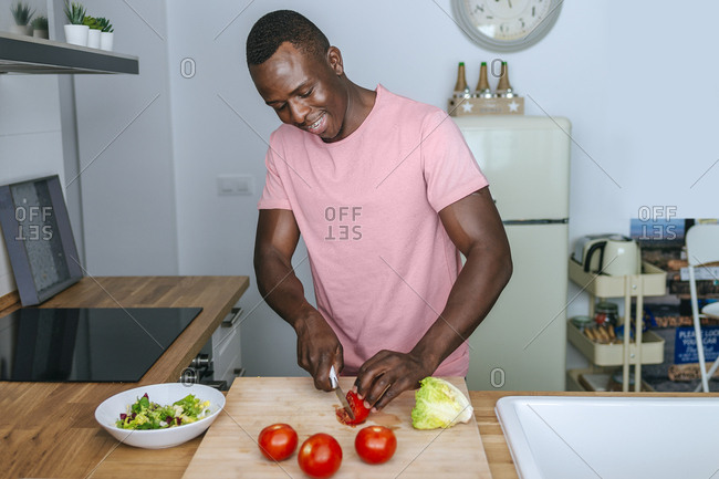 Young man in kitchen cutting tomato for a salad