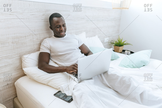 Young man lying in bed using laptop at home