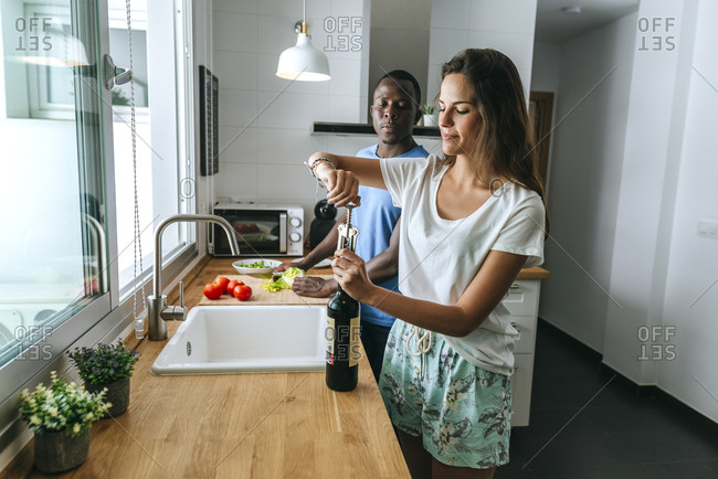 Woman opening bottle of wine next to man in kitchen