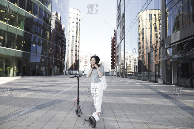 Woman with e-scooter and helmet- modern buildings in the background