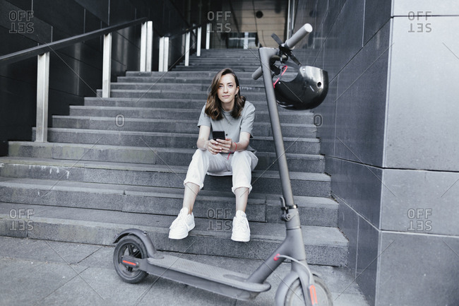 Woman with e-scooter and helmet holding smartphone- sitting on steps