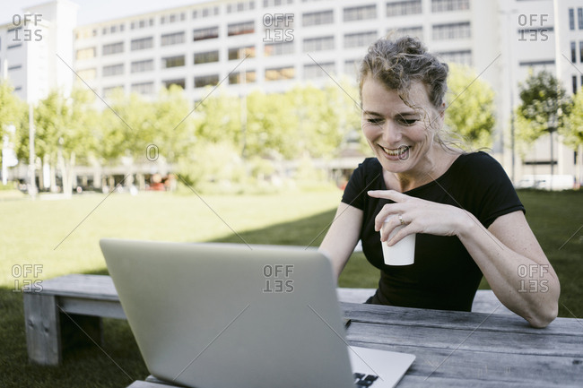 Portrait of smiling mature businesswoman with laptop and coffee to go outdoors