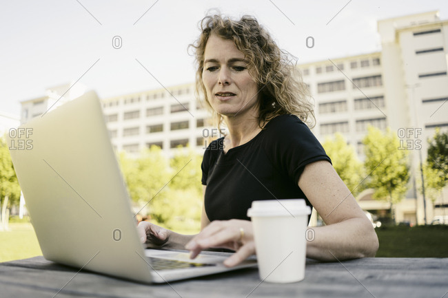 Portrait of mature businesswoman with coffee to go working on laptop outdoors