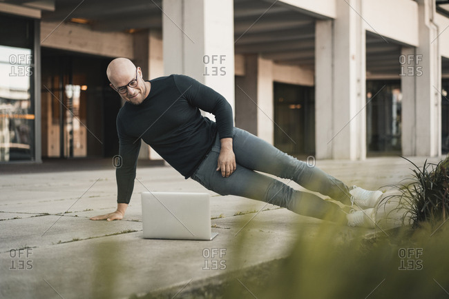 Portrait of smiling man doing pushups while looking at laptop