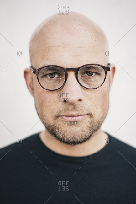 Portrait of serious bald man with beard wearing glasses