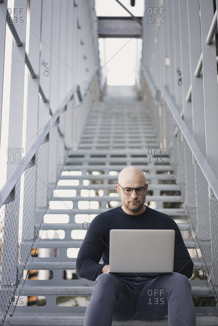 Portrait of bald man sitting on stairs using laptop