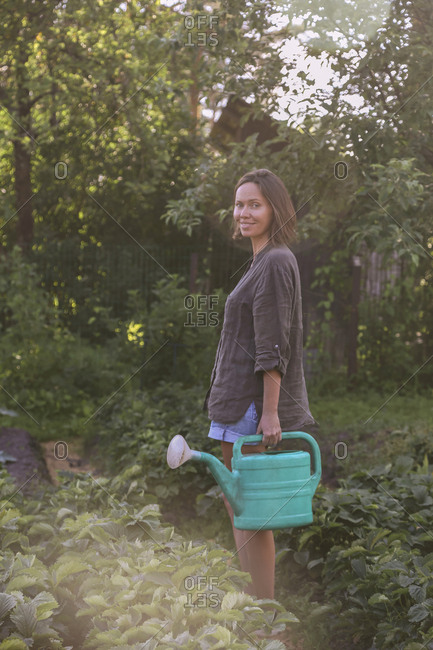 Smiling young woman with watering can in garden