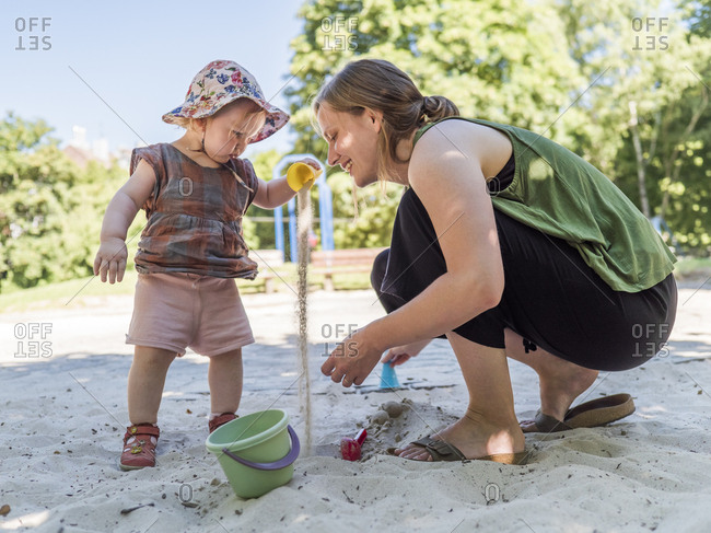 Little girl with her mother in sandbox on playground