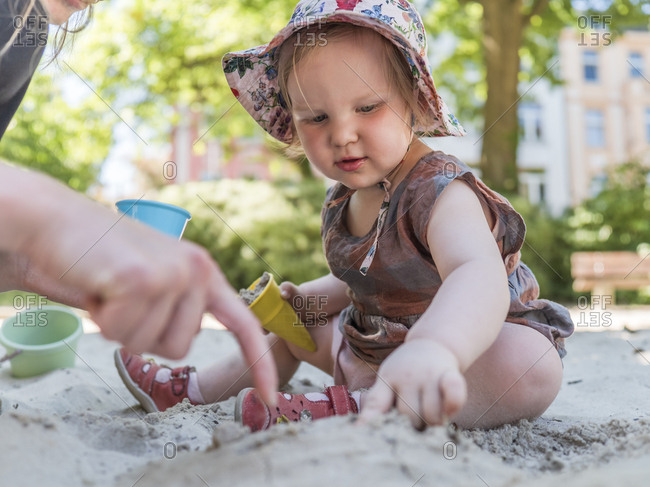 Portrait of little girl with her mother in sandbox on playground