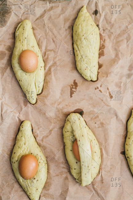Directly above view of fresh brown eggs and dough on paper in kitchen