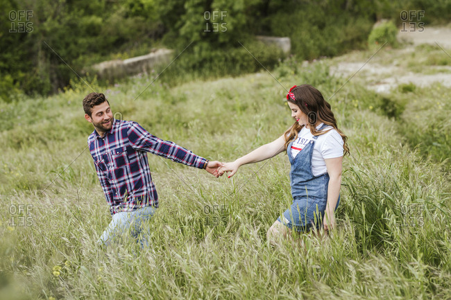 Young couple walking over a meadow holding hands